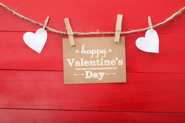 Happy Valentine's Day card with hearts and clothespins on red wood