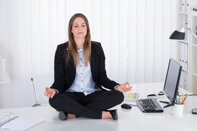Young Beautiful Businesswoman Doing Yoga In Office