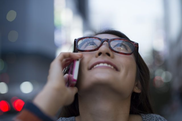 Young women are the phone while looking up at the sky